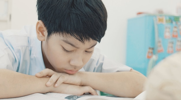 Asian child in student uniform to do homework at home.