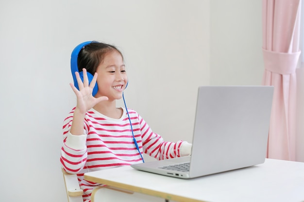 Asian child study online learning class by video call on laptop with teacher