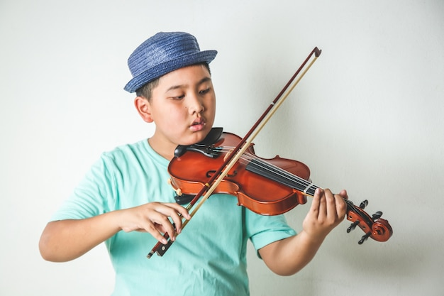 Asian children are playing violin instruments in the classroom.