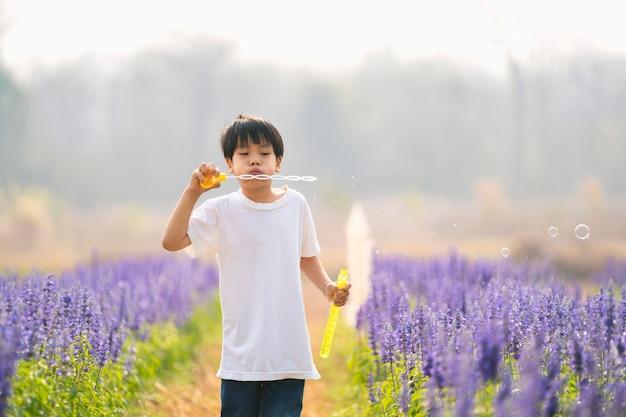 庭の花でシャボン玉を吹いて楽しんでいるアジアの子供たちの男の子