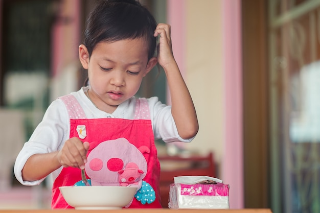 Asian children cooking with not understand at home