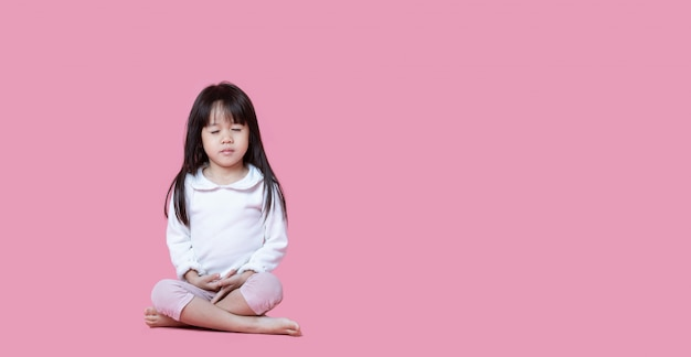 Asian children cute or kid girl sit for meditation with peace and relax on pink