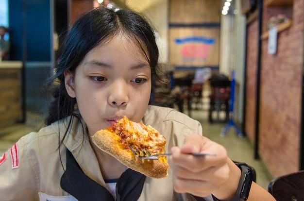 Asian children eat pizza