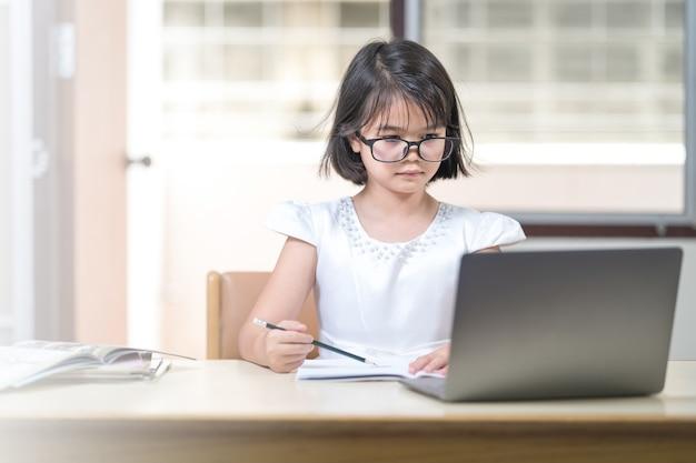 Студентка азиатских детей с очками учится онлайн, делая домашнее задание на компьтер-книжке дома. концепция образования stock photo