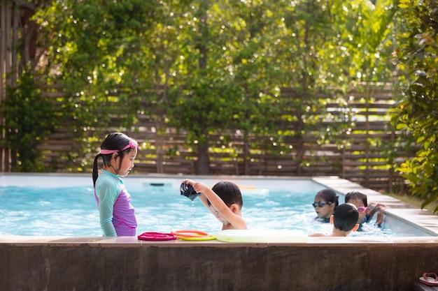 아시아 어린이 소녀들과 소년들은 물놀이를 하고 수영장에서 함께 즐겁게 수영합니다. 여름 활동과 어린 시절의 생활 방식 개념.