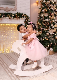 Asian children hug and swing on a rocking horse near the tree and fireplace