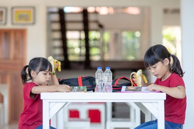 식당에서 점심이나 아침 식사를 하는 아시아 어린이들이 즐거운 시간을 보내고 있습니다