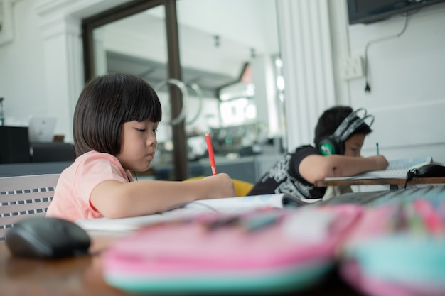 Asian children is learning online computer, home school