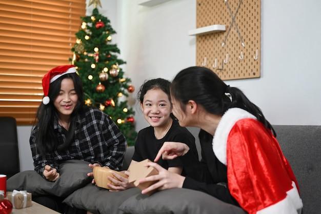 아시아 어린이들은 선물 상자를 열고 집에서 크리스마스를 축하합니다.