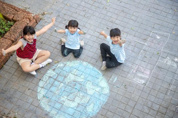 아시아 어린이들은 야외에서 놀고 있습니다. 어린 소녀는 포장, 아스팔트에 세계 색 분필의 지도와 함께 행성 지구를 그립니다. 지구, 평화의 날 콘서트.