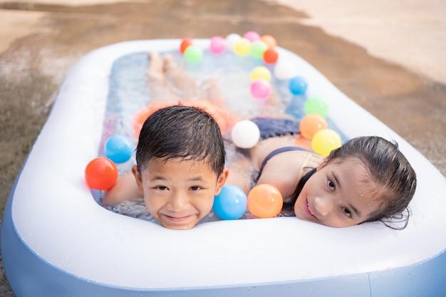 小さなスイミングプールで夏に遊んでいるアジアの子供たち