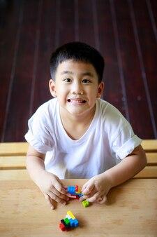 自宅のリビングルームで子供のおもちゃを遊んでいるアジアの子供たち