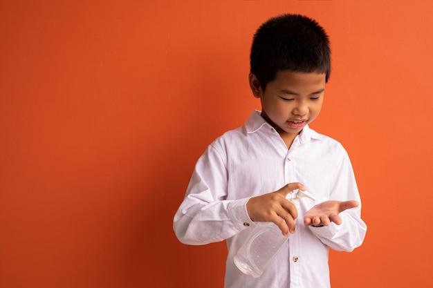アジアの子供たちがジェルで手を消毒します。