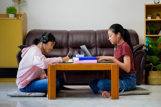 アジアの子供たちは自宅でeラーニングを使って独学します。オンライン教育と独学とホームスクーリングの概念。