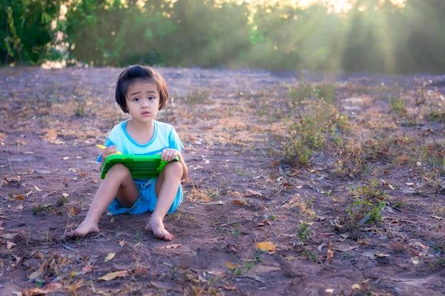 Азиатские дети сидят и рисуют на чертежной доске посреди красивой природы на закате.