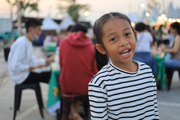 Азиатские дети сидят и едят на фестивале еды в дневное время