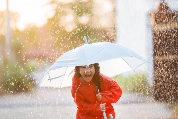 雨の中で傘をさしているアジアの子供たちはレインウェアを着ています。