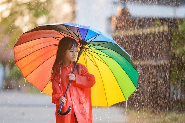 Азиатские дети раскидывают зонтики, играют под дождем, на ней плащ.