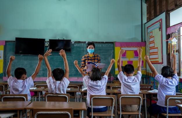 Азиатские дети, учащиеся носят маску для лица, учатся в классе в начальной школе, ученики поднимают руки, чтобы ответить на вопросы, которые им задают учителя