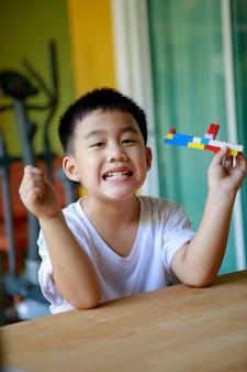 アジアの子供たちの歯を見せる笑顔は健康的な穏やかな歯を示しています