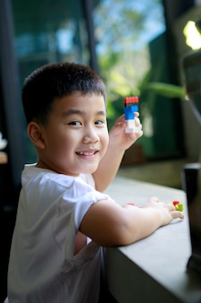 Asian children toothy smiling face playing kid toy at home living room