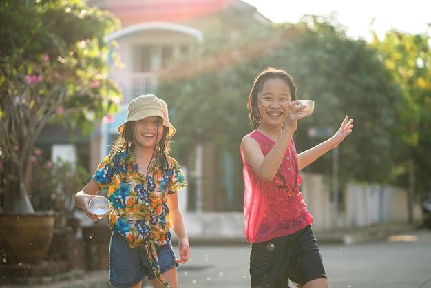 매우 더운 날씨에 친구에게 물 튀김 총을 사용하는 아시아 어린이, songran 축제는 태국에서 매우 인기있는 축제입니다