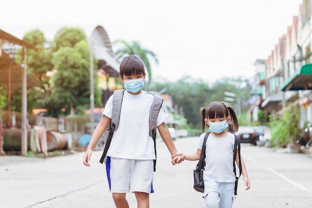 얼굴 마스크를 쓰고 학교 가방을 들고 아시아 어린이