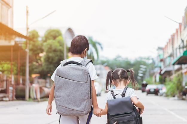 안면 마스크를 쓰고 학교 가방을 들고 아시아 어린이