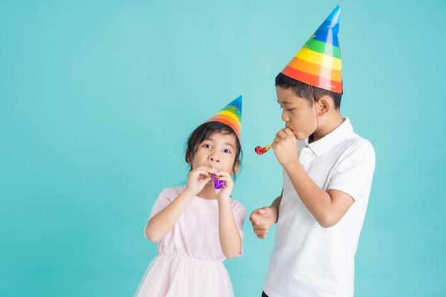 服とマスクを身に着けているアジアの子供たち。パーティーに行く