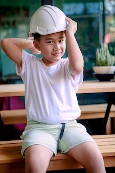 웃는 얼굴로 엔지니어 헬멧을 쓰고 아시아 어린이