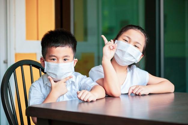 防護マスクを身に着けているアジアの子供たちが自宅の学校で勉強