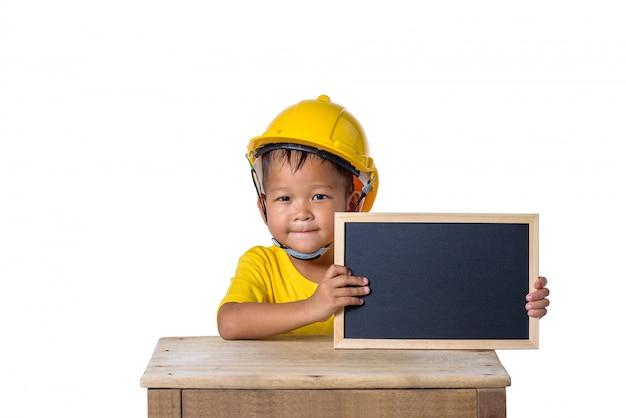 안전 헬멧을 착용하고 흰색 배경에 고립 된 칠판과 함께 웃고 아시아 어린이. 어린이와 교육 개념