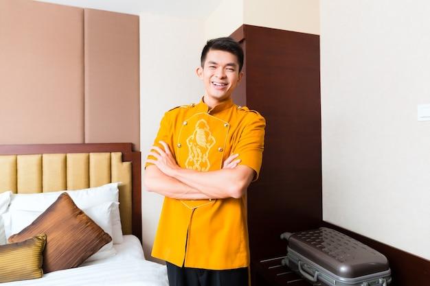 高級ホテルの部屋にゲストのスーツケースを持って来るアジアの中国の手荷物ポーターまたはベルボーイまたはページ