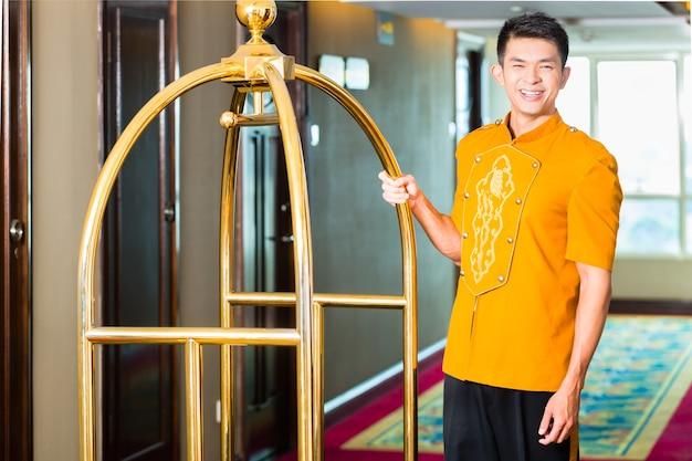 Азиатский китайский носильщик или посыльный или паж, приносящий чемоданы гостей с закрытым фургоном в номер отеля