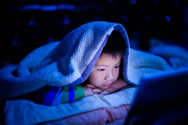 Asian chinese boy playing smartphone on bed, kid use phone and play game, addicted game and cartoon,