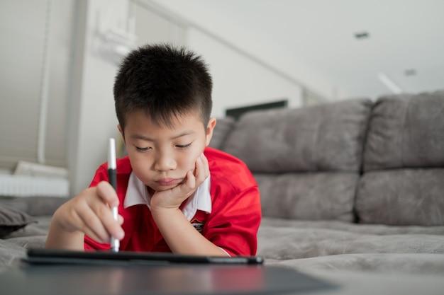 스마트폰을 하는 아시아 중국 소년 아이는 전화를 사용하고 게임에 중독된 게임과 만화를 사용합니다.
