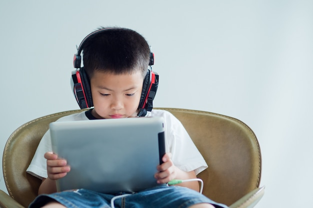 Asian chinese boy playing tablet, kid addicted game and cartoon,