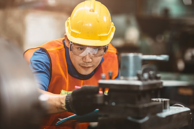 Asian chinese engineer worker wearing safety suit helmet and eyes protection glasses focus at work inspection and checking production process on factory.