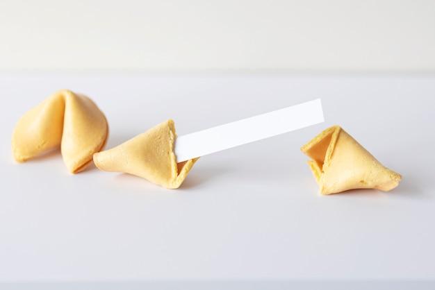 흰색 테이블에 텍스트를 위한 빈 종이가 있는 아시아 중국 포춘 쿠키