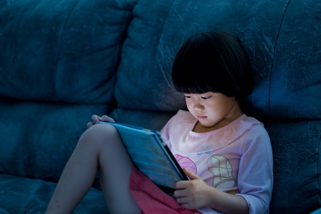 Asian chinese girl playing smartphone, watching smartphone, kid use phone and play game, child use mobile, addicted game and cartoon