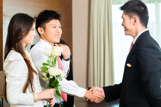 Asian chinese hotel manager or director or supervisor welcome arriving vip guests with roses on arrival in luxury or grand hotel