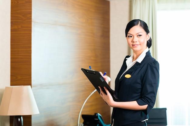아시아 중국 가정부 관리자 또는 보조원이 깔끔함에 대한 체크리스트를 사용하여 호텔의 객실 또는 정장을 통제하거나 점검합니다.