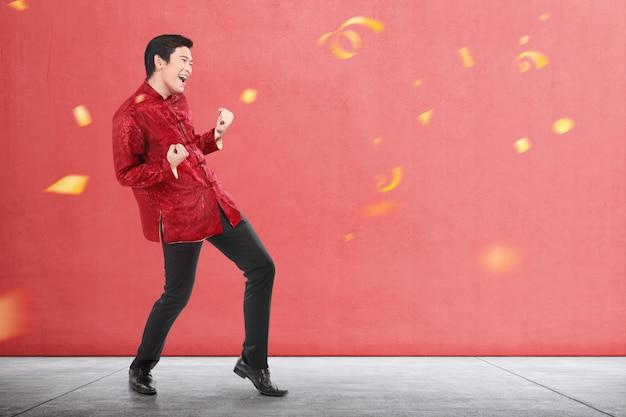 An asian chinese man in cheongsam dress celebrates chinese new year