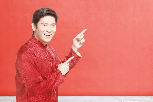 An asian chinese man in cheongsam dress celebrates chinese new year