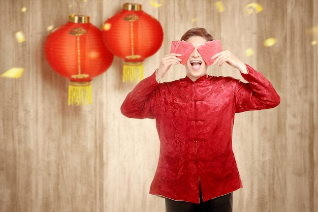 An asian chinese man in a cheongsam dress holding red envelopes