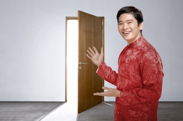 An asian chinese man in cheongsam dress invites into the house to celebrate chinese new year