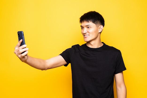Азиатский китаец держит телефон над изолированной желтой стеной
