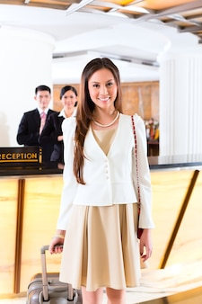 Asian chinese woman arriving at front desk of luxury hotel in business clothes with trolley