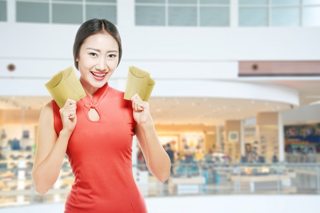 Asian chinese woman in a cheongsam dress holding red envelopes