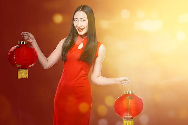 Азиатская китаянка в платье cheongsam держит китайский фонарик. счастливого китайского нового года